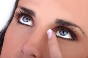 A blue eyed woman putting in her contact lenses
