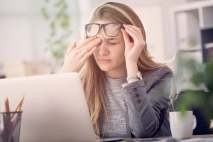 A stressed young lady rubbing her eye while sitting at a desk