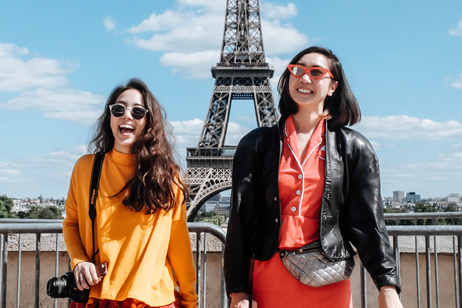 Two beautiful woman wearing sunglasses standing in front of the Eiffel Tower